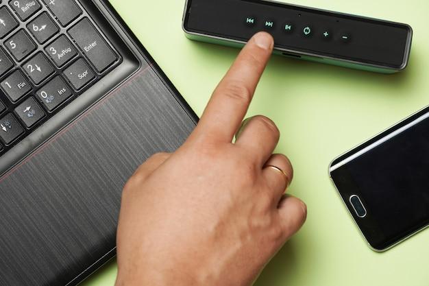 Vue de dessus de la main de l'homme allumant un haut-parleur à côté du téléphone et de l'ordinateur portable