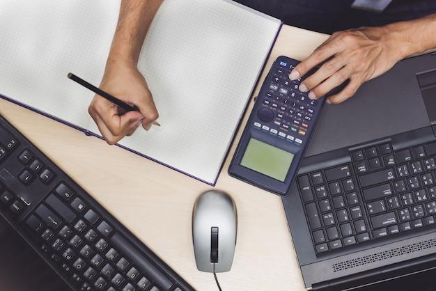 Vue de dessus de la main de l'ingénieur à l'aide de la calculatrice sur la table de travail.