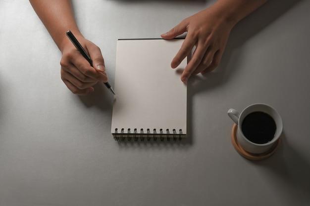Vue de dessus de la main masculine écrit sur un cahier vierge sur un tableau blanc avec une tasse de café