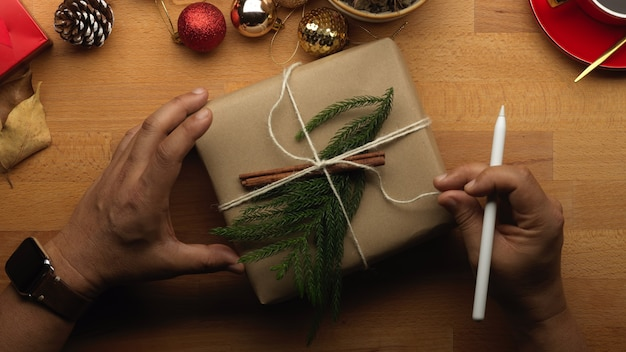 Vue de dessus de la main masculine ouvrant une boîte présente sur table en bois avec des décorations de noël