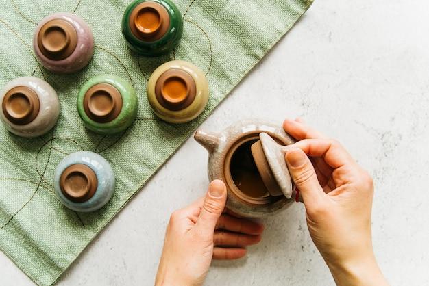 Une vue de dessus de la main ouvrant le couvercle de la théière avec des tasses à thé colorées sur une serviette verte