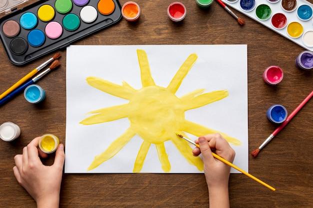 Vue de dessus de la main peignant un soleil