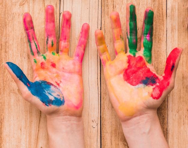 Vue de dessus d'une main peinte colorée mains sur un bureau en bois