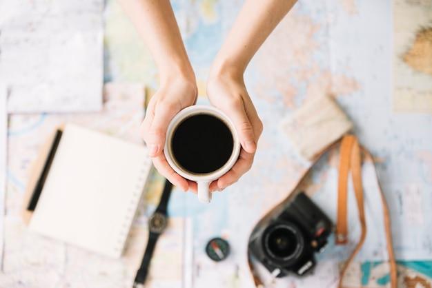 Vue de dessus de la main d'une personne tenant une tasse de café sur la carte de voyage monde floue