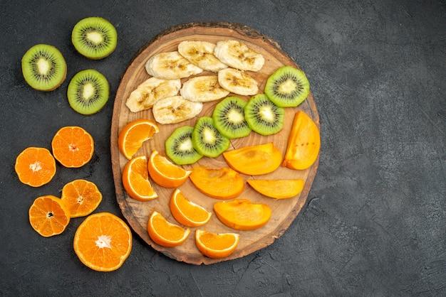 Vue de dessus de la main prenant une tranche d'orange d'un ensemble de fruits frais biologiques naturels sur une planche à découper et autour d'elle sur fond sombre