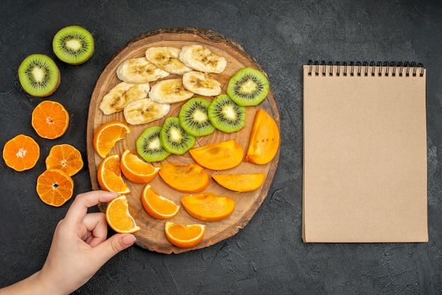 Vue de dessus de la main prenant une tranche d'orange d'un ensemble de fruits frais biologiques naturels sur une planche à découper et un cahier à spirale fermé sur fond sombre