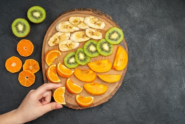 Vue de dessus de la main prenant une tranche d'orange d'un ensemble de fruits frais biologiques naturels sur une planche à découper sur fond sombre