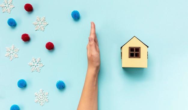 Vue de dessus main séparant la maison en papier et boules décoratives