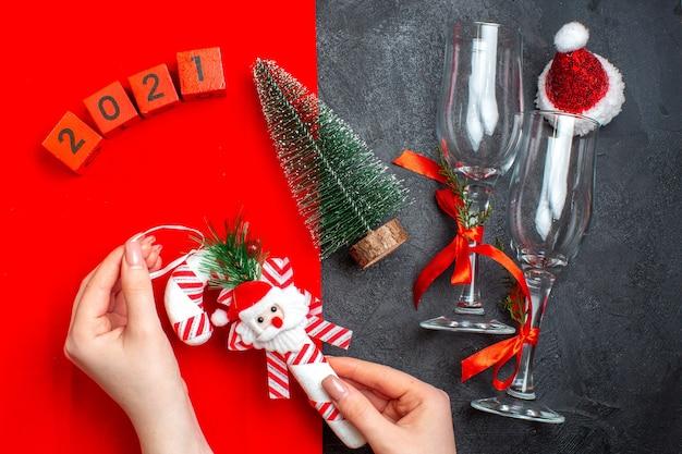 Vue de dessus de la main tenant des accessoires de décoration gobelets en verre numéros d'arbre de noël chapeau de père noël sur fond rouge et noir