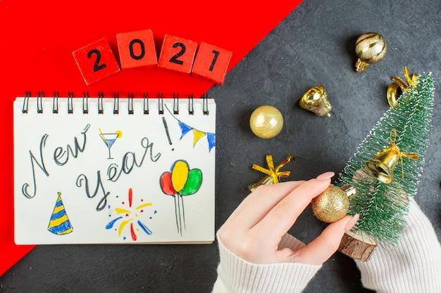 Vue de dessus de la main tenant l'arbre de noël et accessoires de décoration avec des nombres dessinés sur un ordinateur portable sur une table sombre