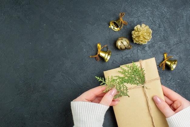 Vue de dessus de la main tenant la boîte-cadeau et les accessoires de décoration sur fond sombre
