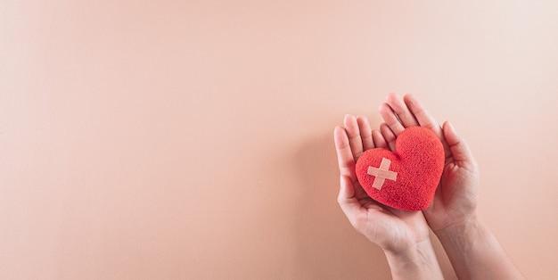 Vue de dessus de la main tenant un coeur rouge sur fond pastel