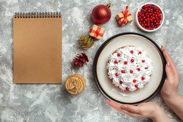 Vue de dessus de la main tenant un délicieux gâteau à la crème de cassis sur une assiette