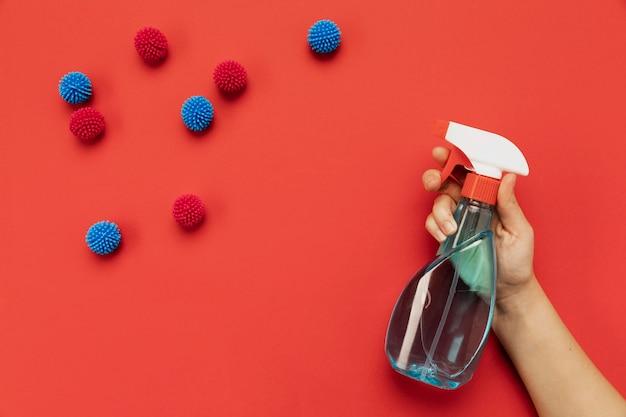 Vue de dessus main tenant un désinfectant avec des boules décoratives
