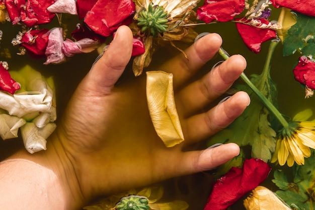 Vue de dessus main tenant des fleurs dans l'eau noire