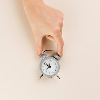 Vue de dessus de la main tenant une petite horloge