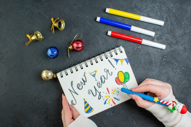 Vue de dessus de main tenant un stylo sur cahier à spirale avec nouvel an écrit et dessins accessoires de décoration sur fond noir
