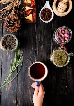 Vue de dessus d'une main tenant une tasse de thé et diverses épices et herbes sur bois noir avec copie espace