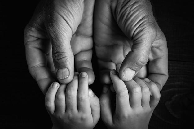 Vue de dessus, mains adultes tenant les mains de l'enfant, concept de soins d'aide à la famille, petites mains dans la main des pères. sur un mur en bois noir. noir et blanc.