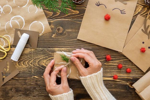 Vue de dessus des mains attachant le cadeau de noël avec de la ficelle et des plantes