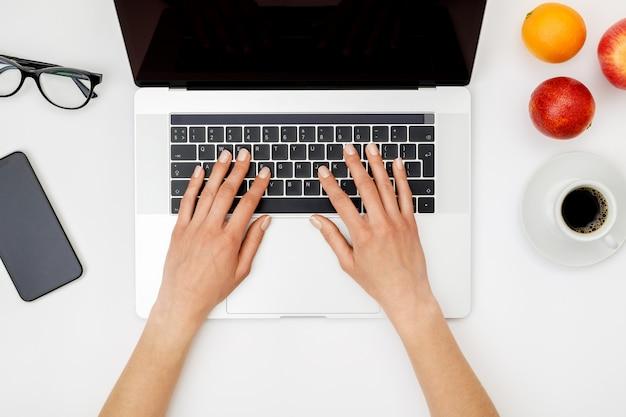 Vue de dessus des mains de la belle femme à l'aide d'un ordinateur portable