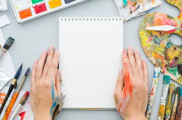 Vue de dessus des mains avec cahier entouré d'éléments de peinture