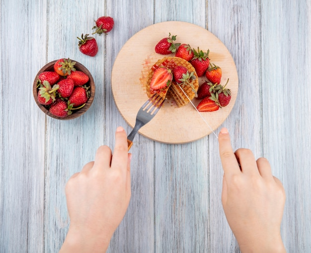 Vue de dessus des mains coupe biscuit gaufre avec fourchette et couteau sur une planche à découper et bol de fraise sur une surface en bois