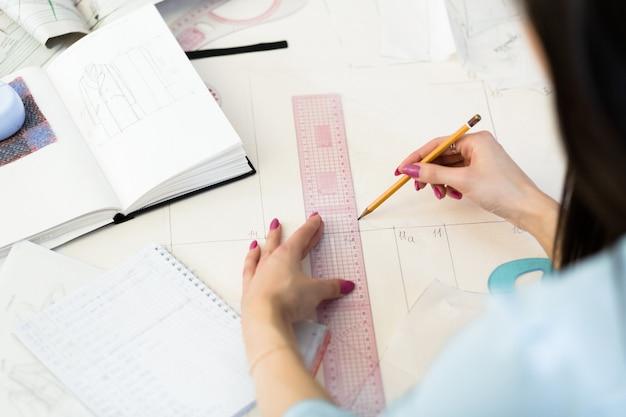 Vue de dessus des mains de couturière faisant un motif sur un papier calque blanc.
