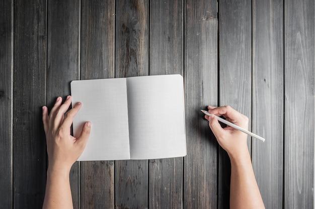 Vue de dessus des mains avec un crayon et cahier ouvert