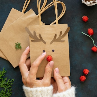 Vue de dessus des mains décorant des sacs-cadeaux de noël renne mignon