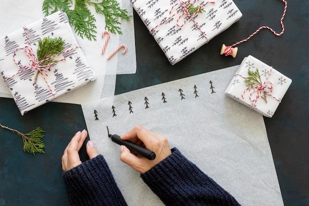 Vue de dessus des mains dessinant des arbres de noël sur du papier d'emballage