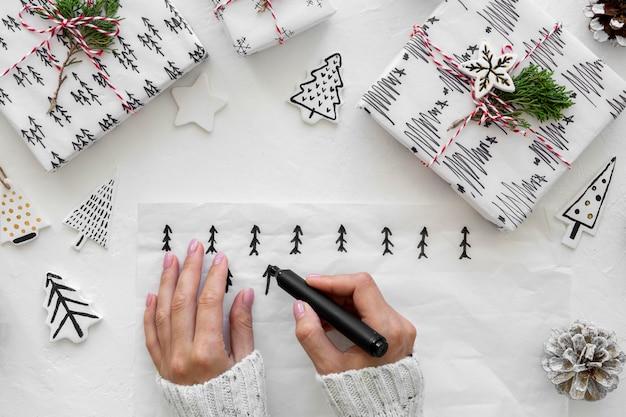 Vue de dessus des mains dessinant des arbres de noël pour des cadeaux