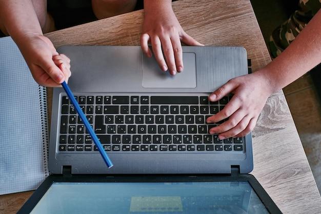 Vue de dessus des mains de deux hommes discutant du nouveau projet et travaillant avec un ordinateur portable
