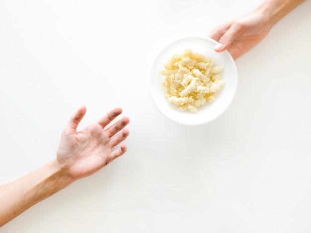 Vue de dessus des mains échangeant de la nourriture