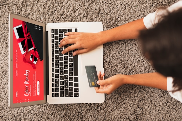 Vue de dessus mains écrivant sur un ordinateur portable et tenant une carte de crédit mock up