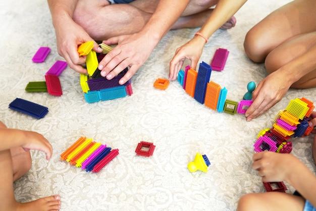 Vue de dessus sur les mains de l'enfant et des parents jouant avec des briques en plastique colorées.