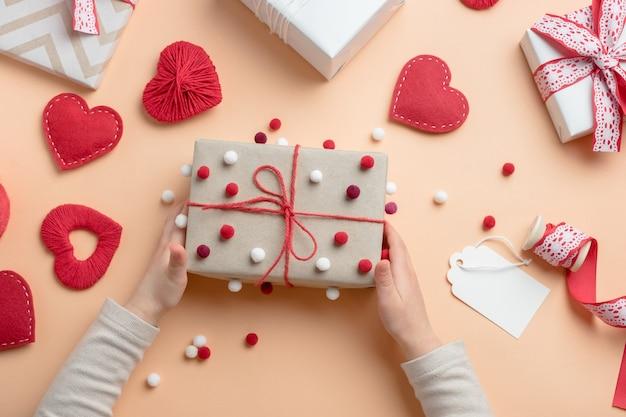 Vue de dessus des mains de l'enfant tenant un cadeau fait main pour la saint-valentin. emballer des cadeaux pour la saint-valentin