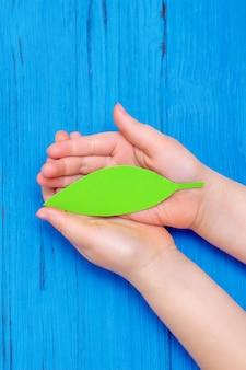Vue de dessus des mains de l'enfant tenant une feuille verte sur fond bleu en bois. espace de copie. concept de protection de l'environnement et jour de la terre.