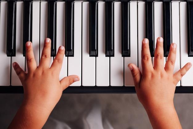 Vue de dessus les mains des enfants jouent sur un synthétiseur électronique