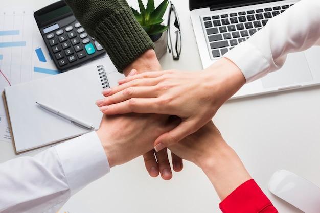 Vue de dessus des mains ensemble sur le bureau