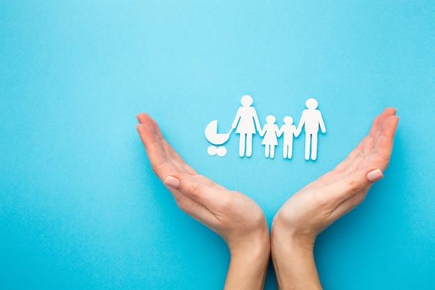 Vue de dessus des mains avec la famille du papier découpé