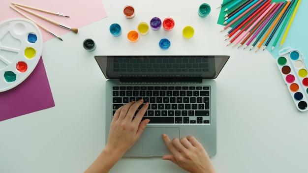 Vue de dessus des mains féminines à l'aide d'un ordinateur portable et de divers outils de dessin colorés