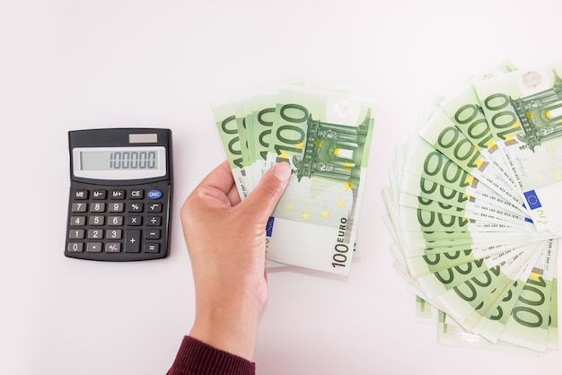 Vue de dessus des mains féminines avec des billets en euros et une calculatrice sur blanc. notion financière.