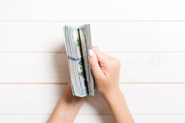 Vue de dessus des mains féminines comptant de l'argent.