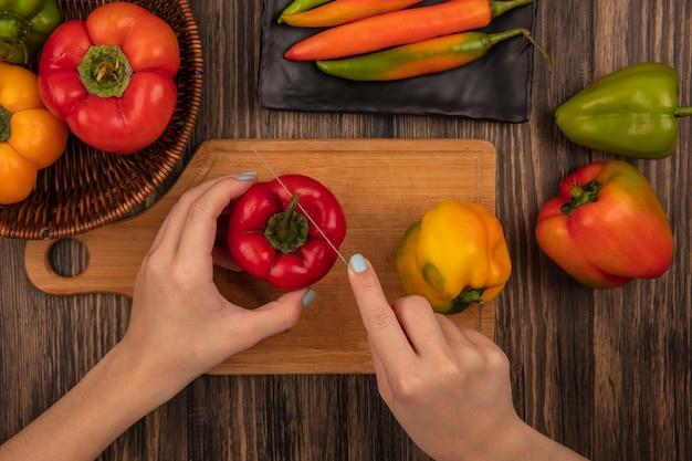 Vue de dessus des mains féminines coupant le poivron aromatique frais sur une planche de cuisine en bois avec un couteau sur une surface en bois