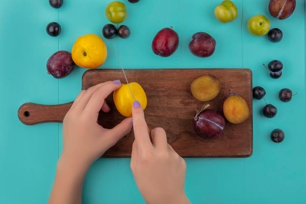 Vue de dessus des mains féminines coupe nectacot avec couteau et pluots sur planche à découper et motif de nectacot de raisin plum pluot sur fond bleu