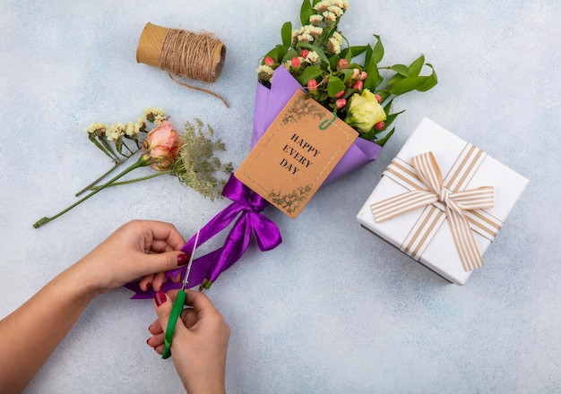 Vue de dessus des mains féminines coupe ruban violet de bouquet de fleurs avec des feuilles sur blanc