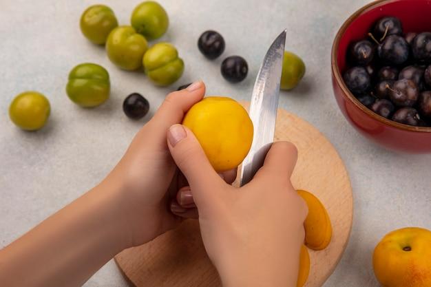 Vue de dessus des mains féminines couper la pêche fraîche avec un couteau sur une planche de cuisine en bois avec un couteau avec des prunes sur un bol rouge sur fond blanc