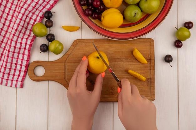 Vue de dessus des mains féminines couper la pêche sur un sanglier de cuisine en bois avec un couteau avec des fruits comme des prunes cerises sloesgreen isolé sur un fond en bois blanc