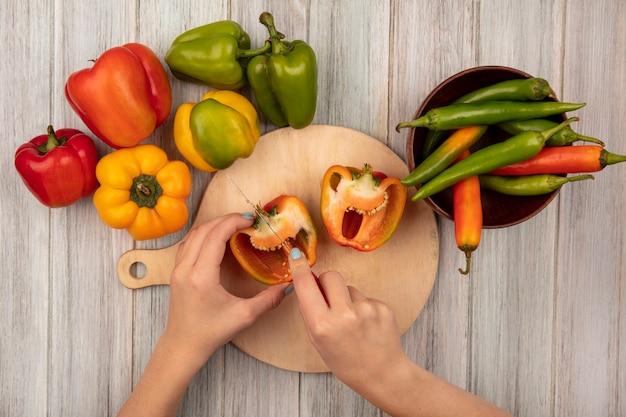 Vue de dessus des mains féminines couper les poivrons orange sur une planche de cuisine en bois avec un couteau sur une surface en bois gris